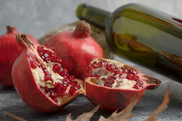 Ripe pomegranate fruits with a bottle of wine on marble surface.