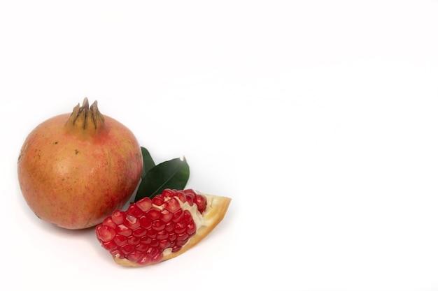 Зрелые плоды граната с листьями граната на белом фоне.