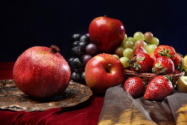 多くの果物の多くに対して古い皿の上の水滴の熟したザクロ