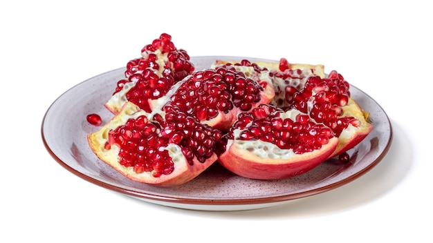 Ripe pomegranate on a plate isolated on white background. healthy fruit.