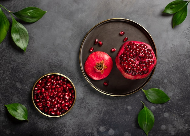 Ripe pomegranate on a plate and peeled pomegranate grain dark surface, close-up, top view