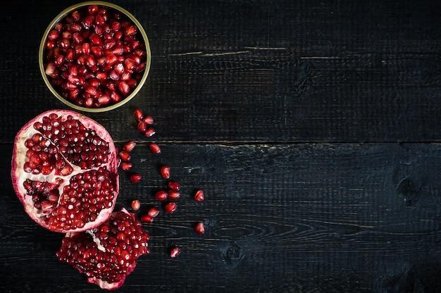 Ripe pomegranate, pomegranate kernels on black wooden.