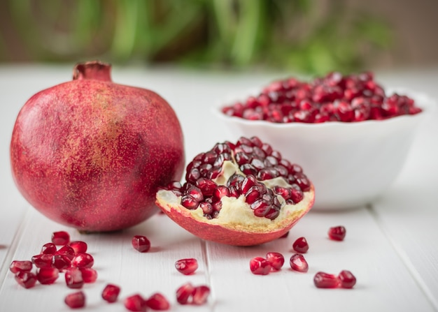 Ripe pomegranate seeds on a white wooden table
