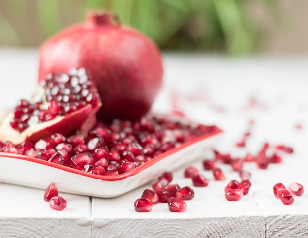 Ripe pomegranate seeds on a white wooden table.