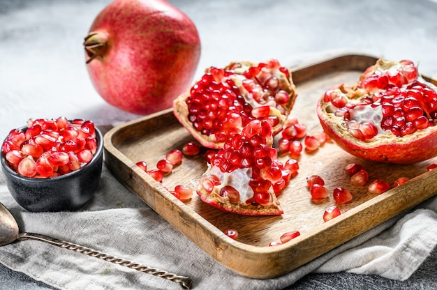Ripe pomegranate and seeds in a wooden bowl. organic fruit.