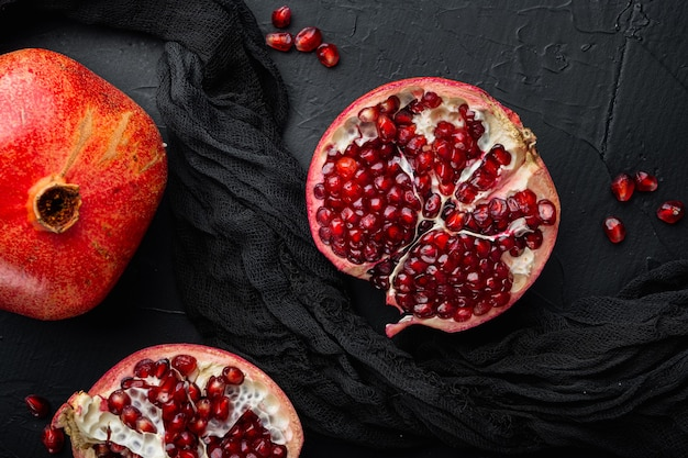 Ripe pomegranate with fresh juicy seeds, on black textured background, flat lay