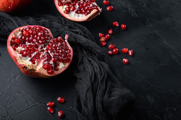 Ripe pomegranate with fresh juicy seeds, on black textured background with space for text