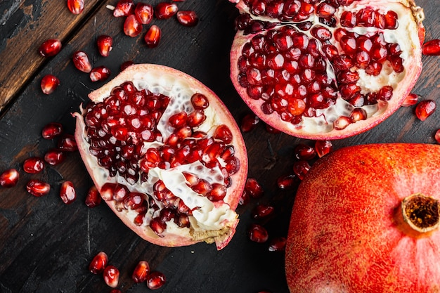 Ripe pomegranate with fresh juicy seeds, on old wooden table, top view