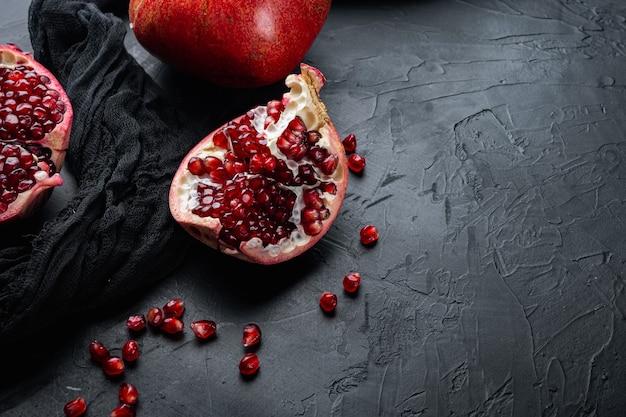 텍스트에 대 한 공간을 가진 검은 질감 배경에 신선한 육즙 씨앗과 잘 익은 석류