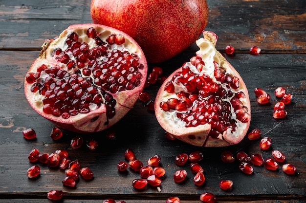 오래된 나무 테이블에 신선한 육즙이 많은 씨앗이 있는 잘 익은 석류