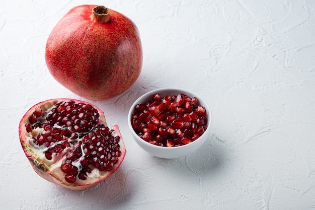 Ripe pomegranate with fresh juicy seeds, on white textured background with space for text
