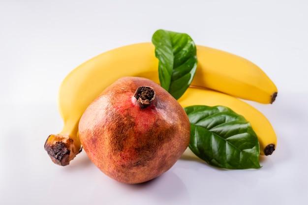 잎과 흰색 바탕에 신선한 바나나와 잘 익은 석류.