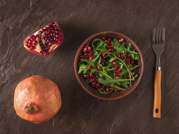 잘 익은 석류와 arugula 샐러드와 석류 씨앗 돌 표면에. 다이어트 채식 샐러드. 평평하다.