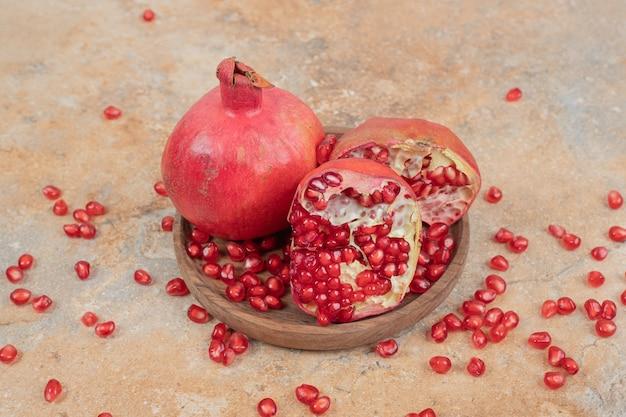Спелые гранаты и семена на деревянной тарелке.