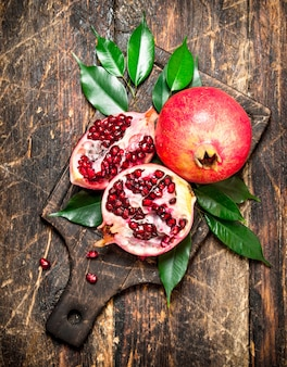 Ripe pomegranates on a cutting board. on wooden background.