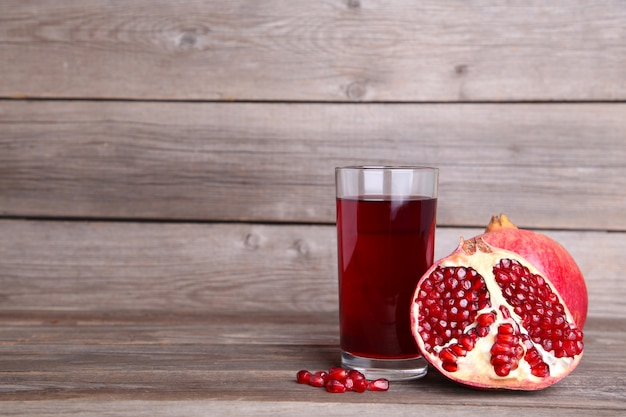 Ripe pomegranates and glass of juice on grey background