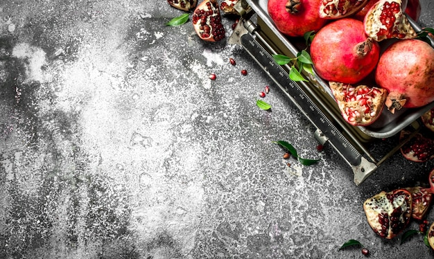 Ripe pomegranates on the scales on a rustic background