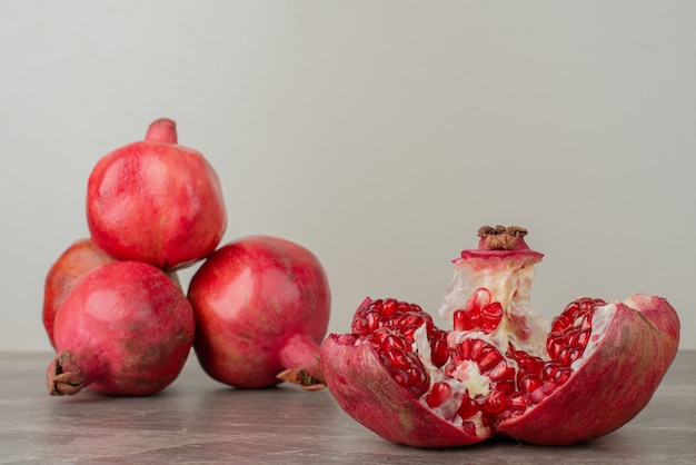 Ripe pomegranates and seeds on marble table.