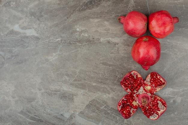 Melograni maturi e semi su marmo.