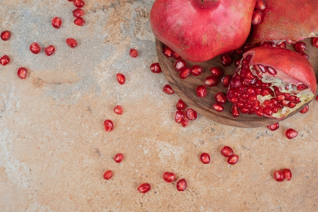 Ripe pomegranates and seeds on wooden plate.