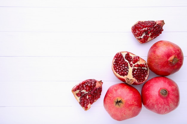 Ripe pomegranates on a white wooden background