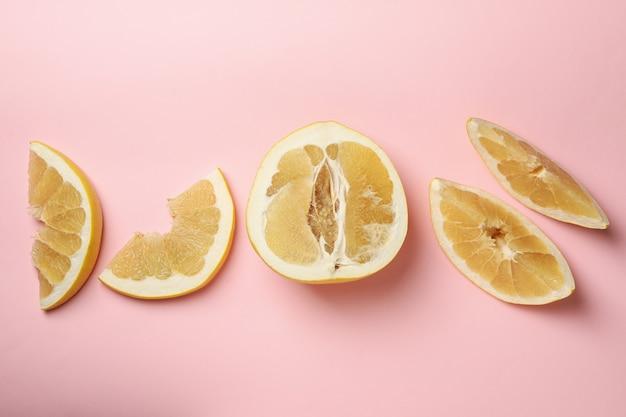 분홍색 배경에 잘 익은 포멜로 과일 조각