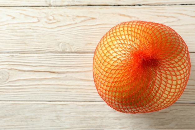 Ripe pomelo fruit on wooden background, space for text
