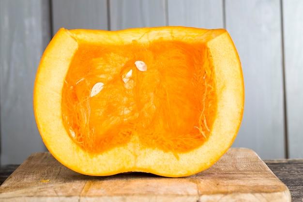 채식 요리를 요리하는 동안 잘 익은 호박을 조각으로 자르고, 달콤한 오렌지색 호박은 부엌의 도마에 조각으로 나눕니다.