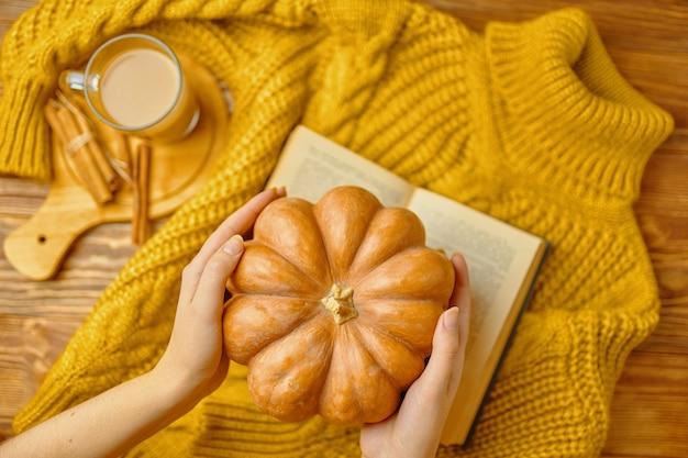 女性の熟したカボチャは、木製のトレイにシナモンスティックが付いたニットセーターの芳香ラテを手渡します...