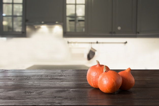 Ripe pumpkin on wooden tabletop in modern kitchen.