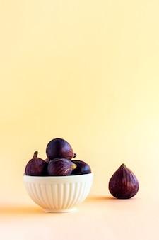明るいパステルカラーの背景に白いセラミックボウルに熟した紫色のイチジクの果実