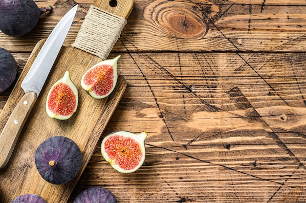 Ripe purple figs on a chopping board. wooden background. top view.