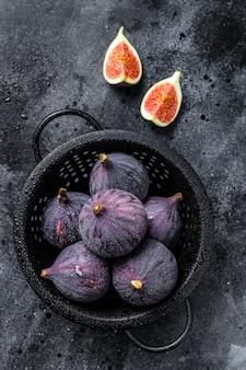 Ripe purple figs in colander. black background. top view.