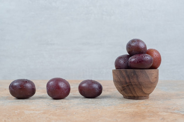 Ripe purple plums in bowl on marble background.