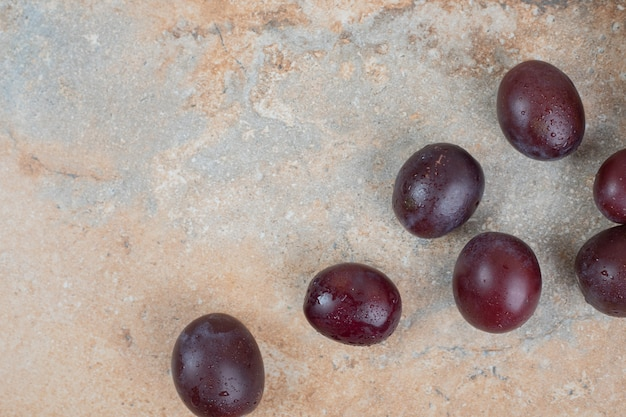 Ripe purple plums on marble background.