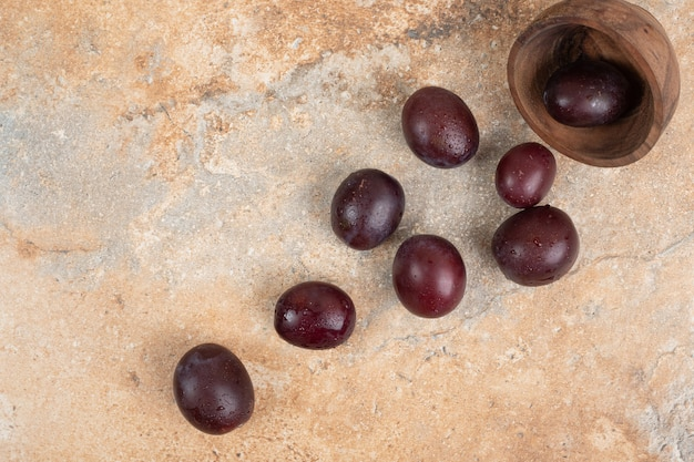Ripe purple plums out of bowl on marble background.