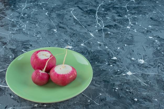 Ravanello maturo su un piatto, sullo sfondo di marmo.