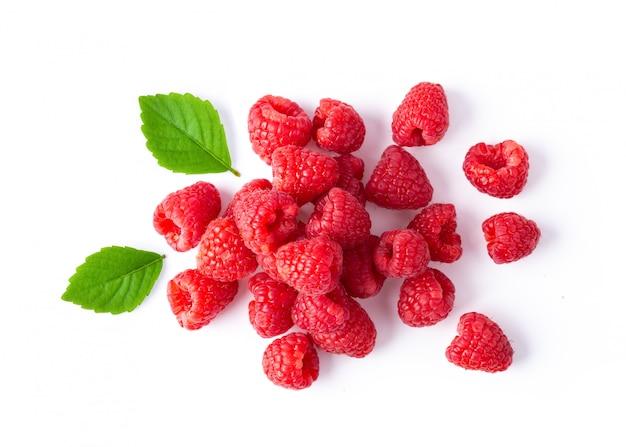 Ripe raspberries on white table.