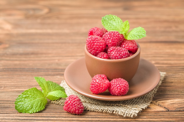 Ripe raspberries with green mint leaves in brown cup and saucer on sackcloth and wooden background.
