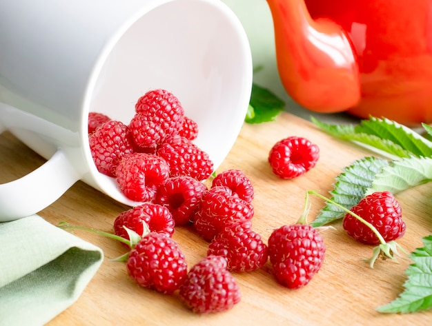 Ripe raspberry berries on a wooden background are poured out of a white cup.