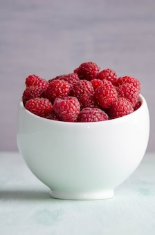 Ripe raspberry in white bowl on the table