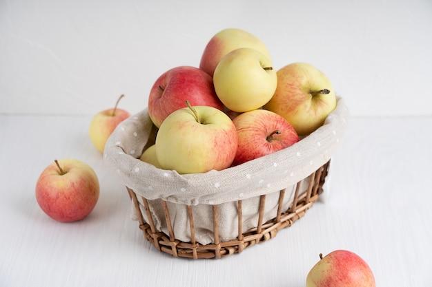 白い木製のテーブルの籐のバスケットに熟した生のリンゴ