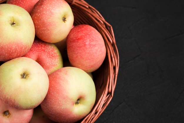 Ripe raw apples in wicker basket on black background with copy space