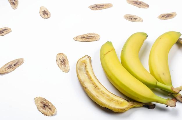 잘 익은 원시 바나나와 말린 바나나 조각 칩 흰색 배경에 흩어져. 과일 칩. 건강한 먹는 개념, 간식, 설탕 없음. 상위 뷰, 복사 공간.