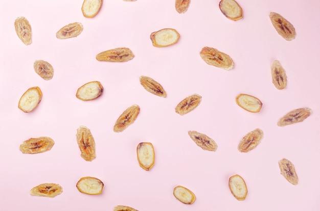 익은 생 바나나와 말린 바나나 조각 칩이 흰색 배경에 흩어져 있습니다. 과일 칩. 건강한 식생활 개념, 간식, 설탕 없음. 상위 뷰, 복사 공간입니다.