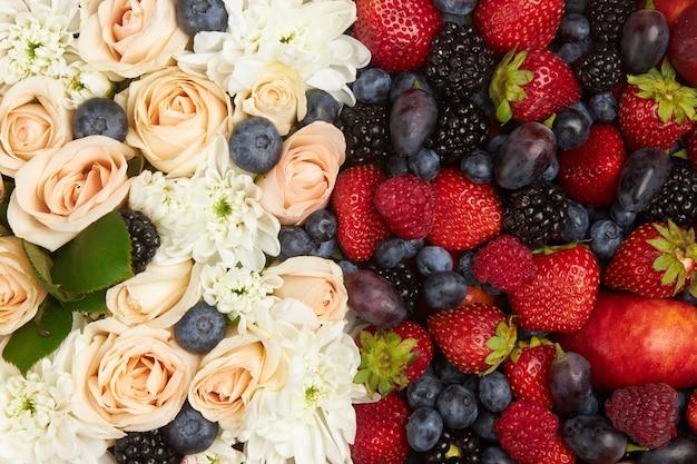 Спелые красные и черные фрукты, белые и розовые цветы в качестве праздничного фона или фона