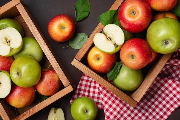 さびた背景の木箱に熟した赤と緑のリンゴ。テキスト用のスペースがある上面図。