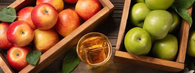 熟した赤と緑のリンゴを木製の箱に入れ、白い花の枝とフレッシュジュースのグラスを木製のテーブルに置きます。パノラマの上面図。