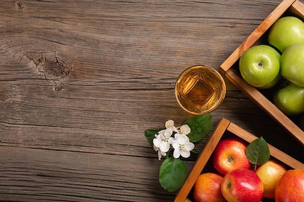 熟した赤と緑のリンゴを木製の箱に入れ、白い花の枝とフレッシュジュースのグラスを木製のテーブルに置きます。テキスト用のスペースがある上面図。
