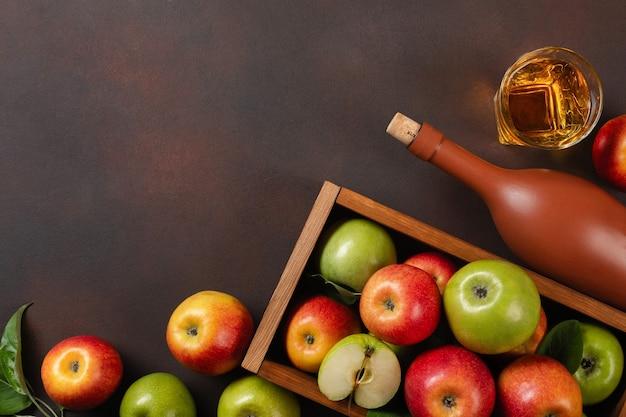 さびた背景に白い花、ガラス、サイダーのボトルの枝と木製の箱に熟した赤と緑のリンゴ。テキスト用のスペースがある上面図。